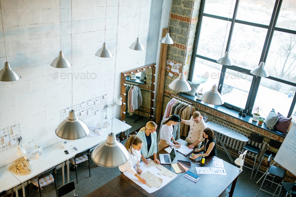 Group of young contemporary creative designers working over new collection - Stock Photo - Images