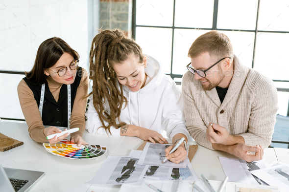 Group of young creative designers of clothes working over new fashion sketches