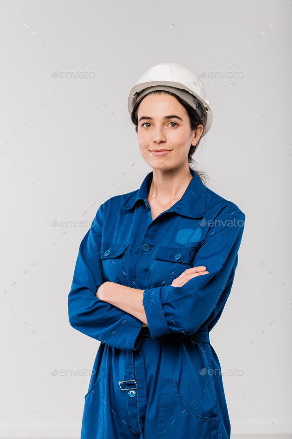 Pretty young cross-armed female engineer in blue workwear and safety helmet - Stock Photo - Images