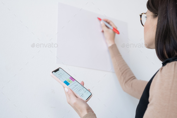 Young businesswoman or coach holding smartphone with flow chart - Stock Photo - Images