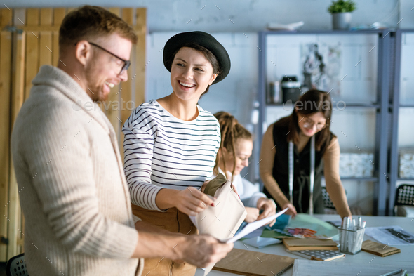 Cheerful female and her colleague choosing textile for new fashion collection - Stock Photo - Images