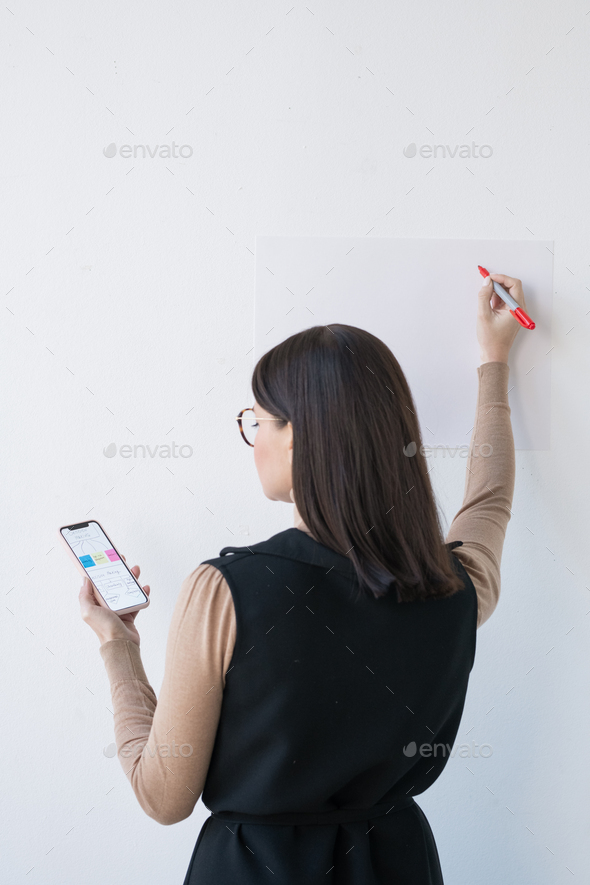 Rear view of elegant businesswoman or coach with smartphone making presentation - Stock Photo - Images