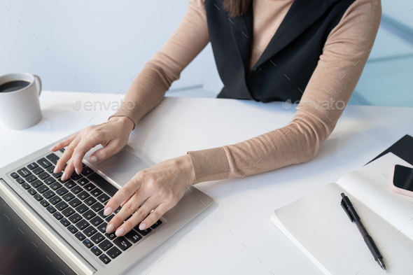 Hands of young businesswoman over laptop keypad during work - Stock Photo - Images