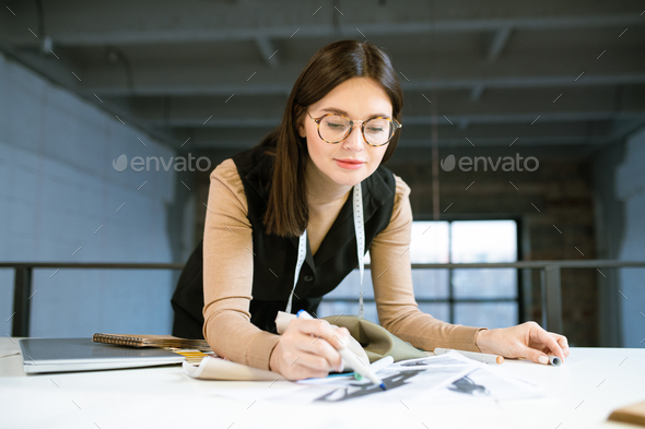Creative young female designer pointing at on of fashion sketches at work - Stock Photo - Images