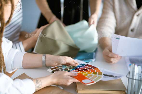Hands of designer holding color palette over desk while working with colleagues - Stock Photo - Images