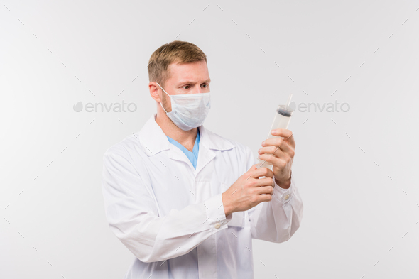 Young male clinician in whitecoat and protective mask holding big syringe - Stock Photo - Images