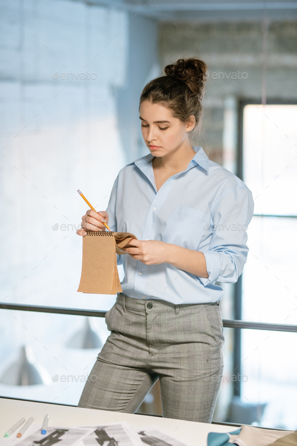 Serious creative designer making sketch in notepad during work in studio - Stock Photo - Images