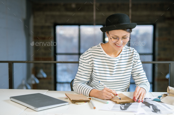 Happy young creative female sitting by desk in studio and drawing fashion sketch - Stock Photo - Images
