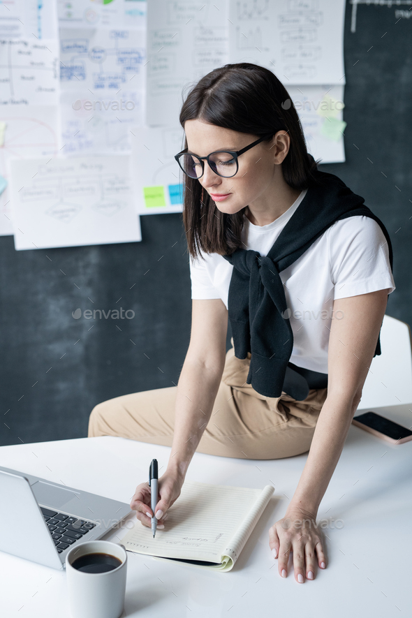 Young contemporary female office worker making notes in front of laptop - Stock Photo - Images