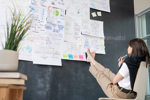 Young barefoot businesswoman sitting on chair in front of blackboard - Stock Photo - Images