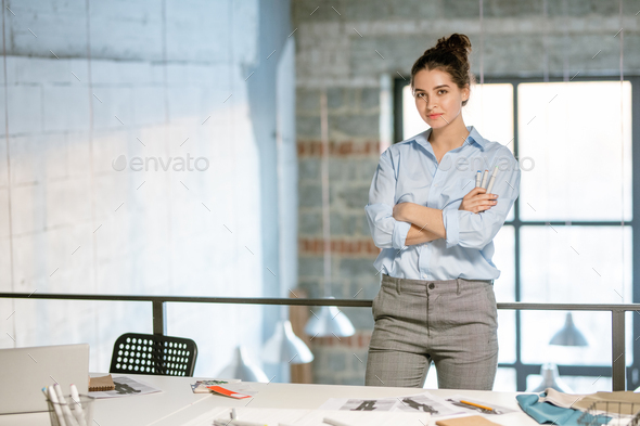 Young successful female fashion designer crossing arms by chest during work - Stock Photo - Images