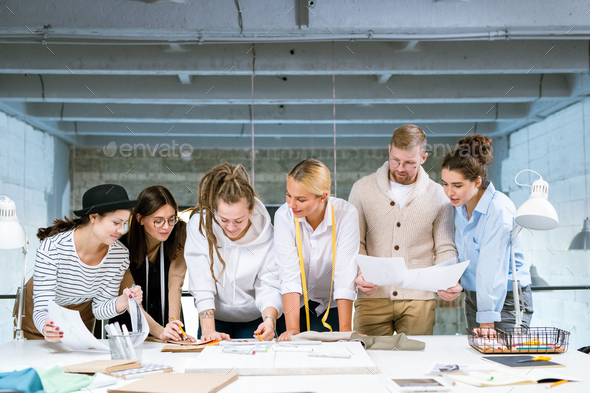 Group of young creative designers discussing stuff for new fashion collection - Stock Photo - Images