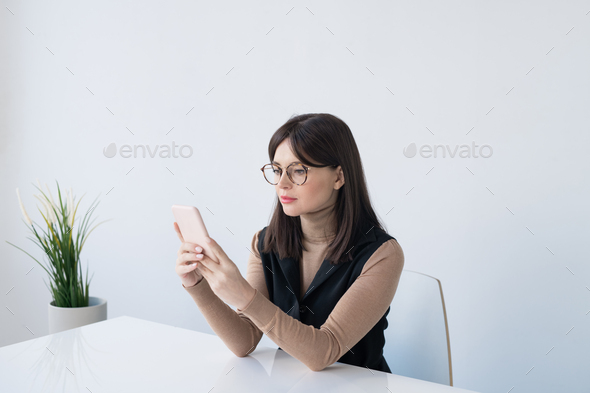 Young brunette businesswoman in smart casual scrolling in smartphone in office - Stock Photo - Images