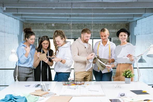 Group of six young creative designers working over new fashion collection - Stock Photo - Images