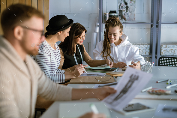 Group of happy young women discussing creative ideas while working in studio - Stock Photo - Images