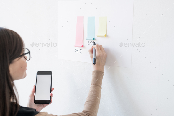 Young female broker writing down percentage under paper chart on whiteboard - Stock Photo - Images