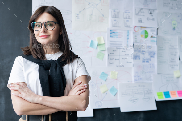 Pretty young businesswoman in eyeglasses crossing arms by chest - Stock Photo - Images