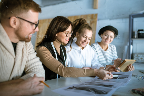 Young creative designers discussing fashion sketches while working in studio - Stock Photo - Images
