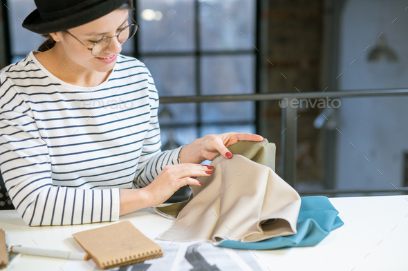 Pretty young fashion designer looking at piece of textile while choosing fabric - Stock Photo - Images