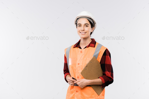 Successful young female engineer in protective helmet and orange jacket - Stock Photo - Images