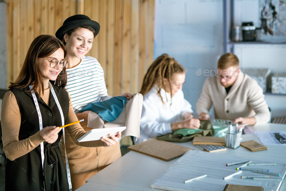 Creative fashion designers with tablet discussing new collections and trends - Stock Photo - Images
