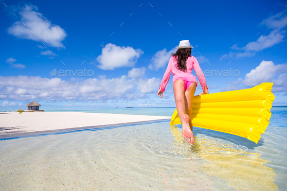 Young happy woman relaxing with air mattress on the beach - Stock Photo - Images