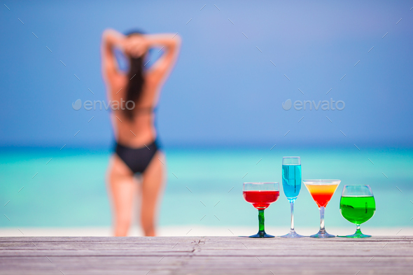 Exotic tasty cocktails in outdoor cafe background turquoise sea and girl - Stock Photo - Images