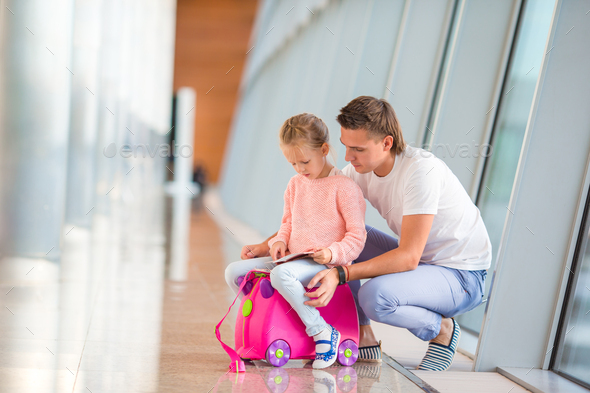 Happy dada and little girl with boarding pass at airport terminal waiting the flight - Stock Photo - Images