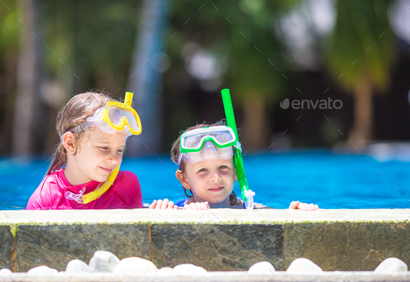 Adorable little girls having fun in outdoor swimming pool on summer vacation - Stock Photo - Images
