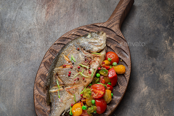 Close view of pan fried dorado fish with vegetables - Stock Photo - Images