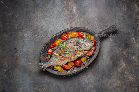 Fried fish with vegetables on cutting board, copy space - Stock Photo - Images