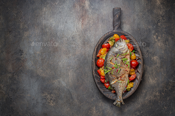 Fried whole fish with vegetables on cutting board, copy space - Stock Photo - Images