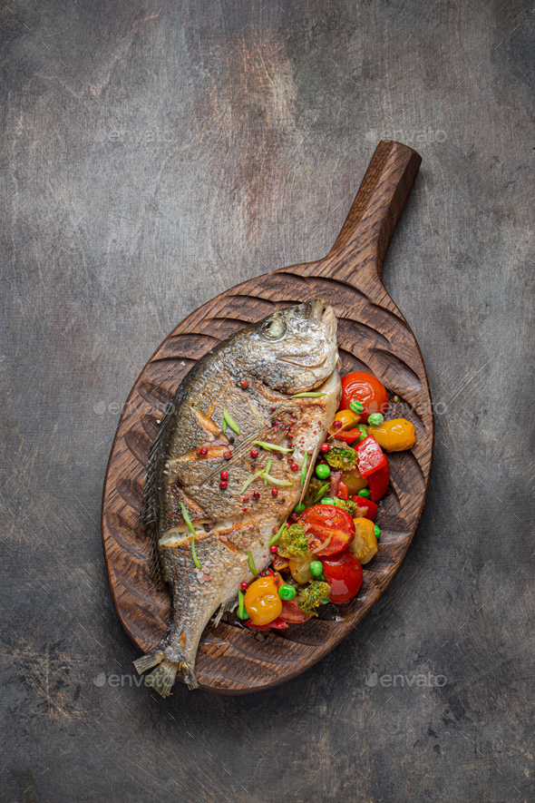 Sea bream fish with vegetables on cutting board, copy space - Stock Photo - Images