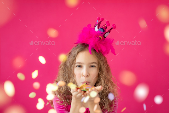 Fancy girl blowing confetti against pink bakground - Stock Photo - Images