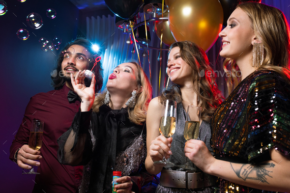 Glamorous girl blowing soap bubbles among friends with flutes of champagne - Stock Photo - Images