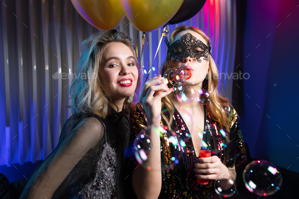 One of two pretty girls blowing soap bubbles with her friend standing near by - Stock Photo - Images