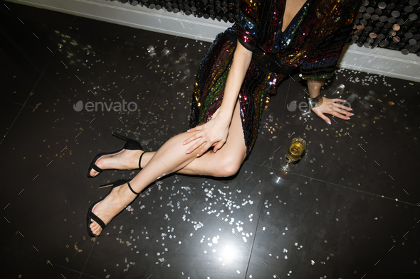 Young glamorous woman in glittering sequin dress relaxing on the floor - Stock Photo - Images
