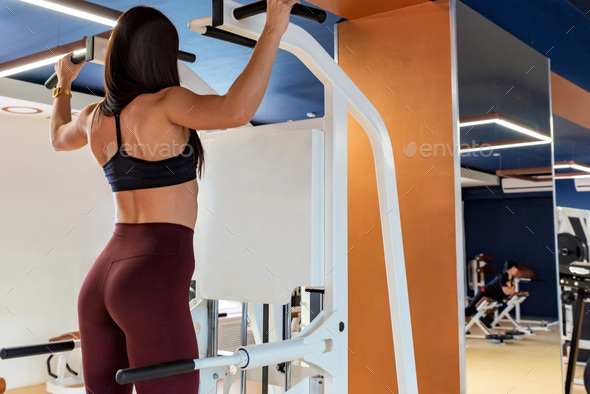 Back view female athlete does back exercises in gym - Stock Photo - Images