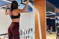 Back view female athlete does back exercises in gym - PhotoDune Item for Sale