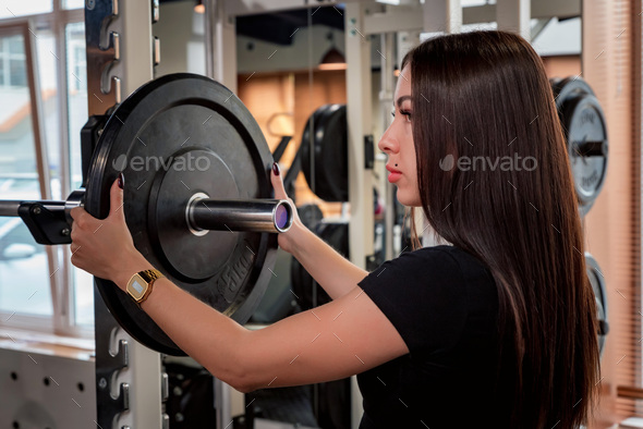 Fitness woman puts plate on barbell side view - Stock Photo - Images