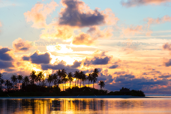 Beautiful sunset with dark silhouettes of palm trees and amazing cloudy sky in tropical island - Stock Photo - Images