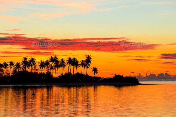 Beautiful sunset with dark silhouettes of palm trees and amazing cloudy sky in Indian island - Stock Photo - Images