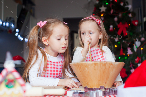 Adorable girls baking gingerbread cookies for Christmas at home kitchen - Stock Photo - Images