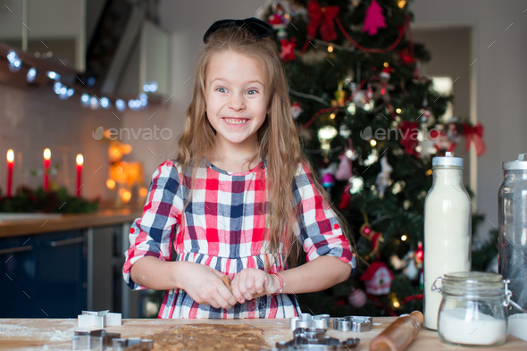 Little adorable girl baking Christmas cookies at home - Stock Photo - Images