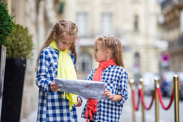 Adorable little girls with map of european city outdoors - Stock Photo - Images