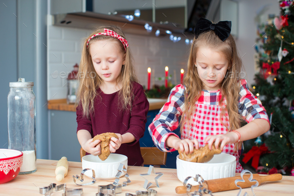 Little happy girls baking gingerbread cookies for Christmas at home kitchen - Stock Photo - Images