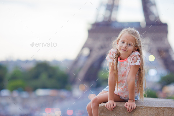 Adorable little girl background the Eiffel tower during summer vacation in Paris - Stock Photo - Images