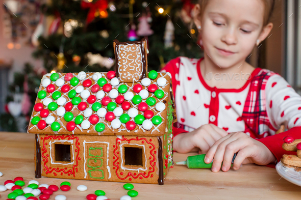 Little adorable girl decorating gingerbread house for Christmas - Stock Photo - Images