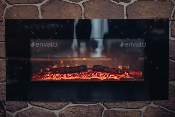 Fireplace with burning logs. Close-up of stony fireplace with burning or smoldering logs on fire - Stock Photo - Images