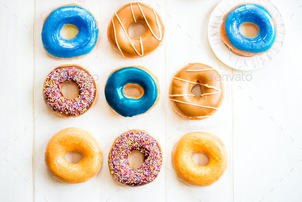 Glazed Doughnuts with colourful sprinkles and icing - Stock Photo - Images